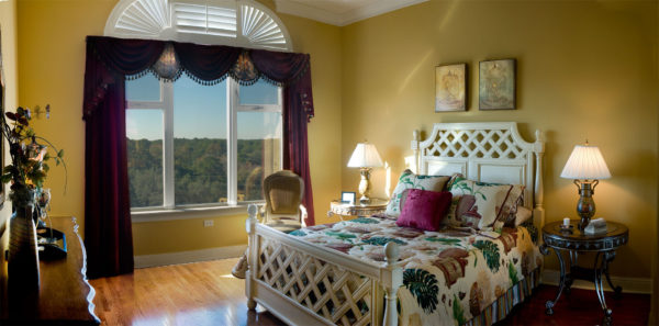 Yellow bedroom, country styled, with windows and purple drapes